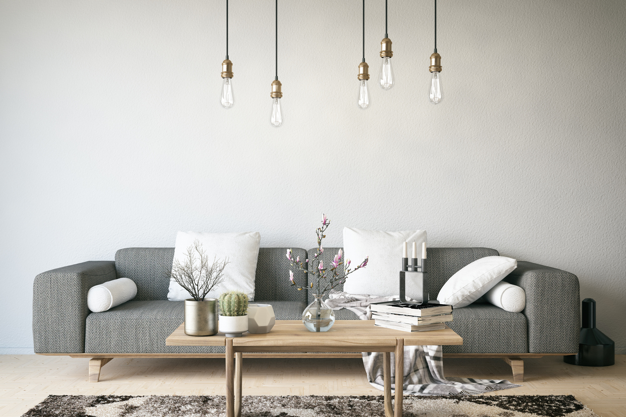 Modern living space redone by an interior designer to include a grey couch, free hanging light bulbs, and a simple table.