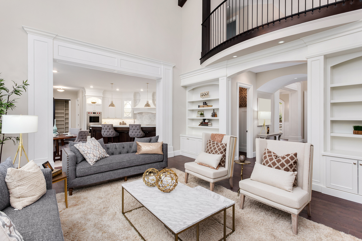 Beautiful living room interior with tall vaulted ceiling, loft area, hardwood floors and fireplace in new luxury home. Has view of kitchen and dining area, and loft. Redone by interior designer